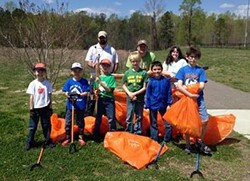 Children stand with rakes and orange bags, ready to volunteer in Warhill.
