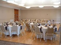 Meeting room with tables and chairs set up with tablecloths